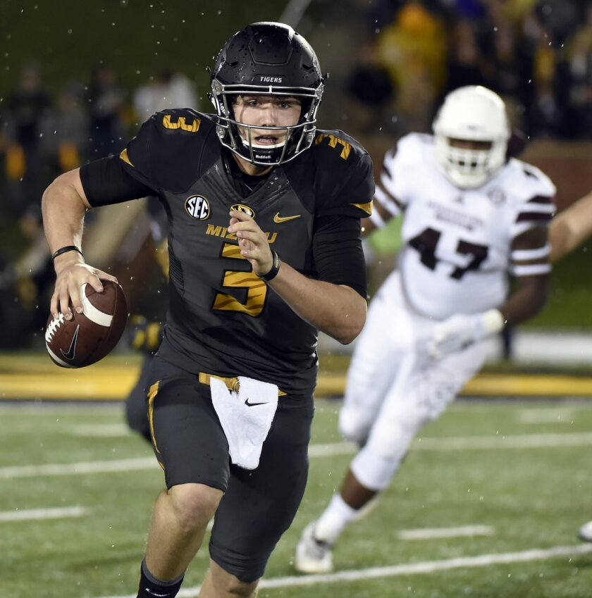 Missouri quarterback Drew Lock, left, scrambles as Mississippi State defensive lineman A.J. Jefferson, right, gives chase during the first half of an NCAA college football game on Thursday, Nov. 5, 2015, in Columbia, Mo. (AP Photo/L.G Patterson)