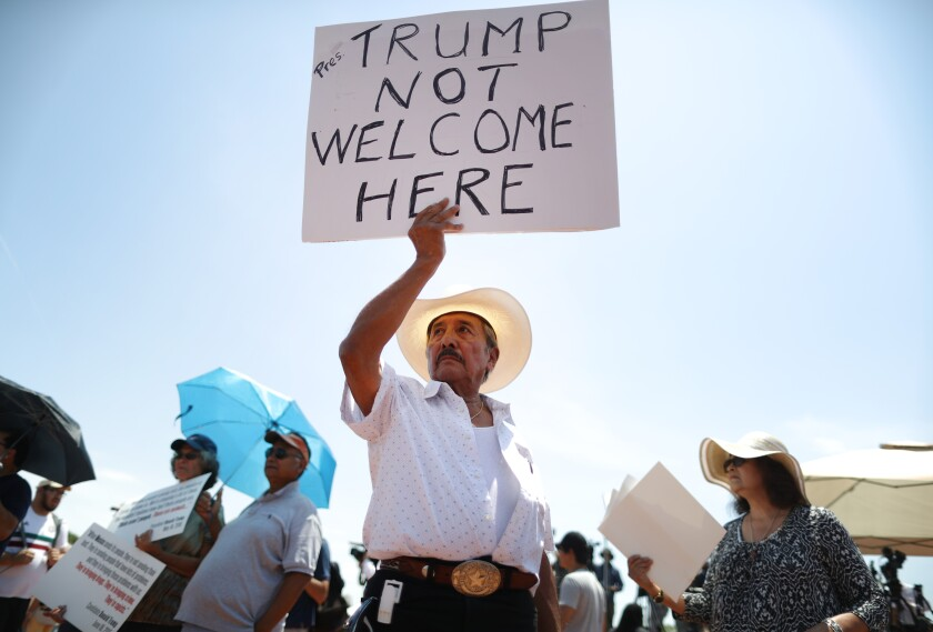 Miguel de Anda, who was born and raised in El Paso, holds up a sign at a protest against President Trump's visit following a mass shooting in the city.