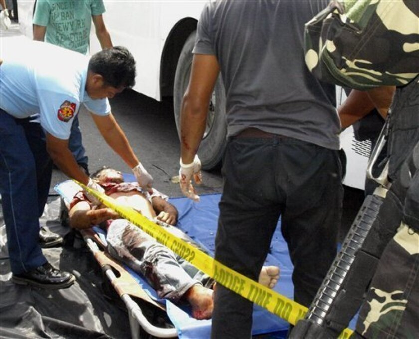 A police investigator looks for identification which belongs to a dead bus passenger after an explosion Thursday, Oct. 21, 2010 in Matalam town in southern Philippines. A bomb ripped through the passenger bus killing at least eight people and wounding 10 in an attack authorities blamed on an exto
