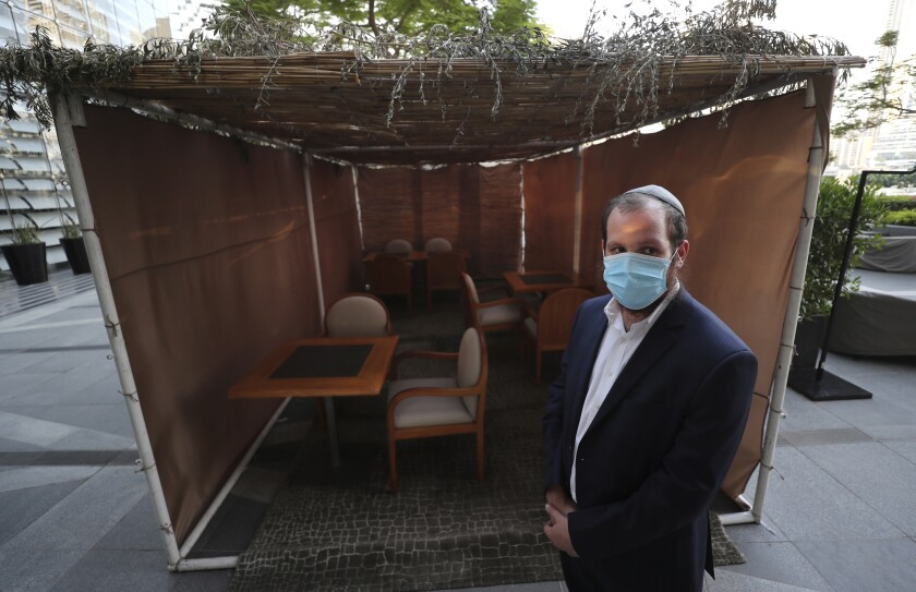 Rabbi Mendel Duchman talks to an Associated Press journalist in front of a sukkah, the temporary shelter where Jews gather to celebrate the weeklong harvest festival of Sukkot, set up at the KAF Kosher Restaurant in the Armani Hotel in Dubai, United Arab Emirates, Monday, Oct. 5, 2020. The sukkah was set up last week outside the first kosher restaurant in the UAE, following a U.S.-brokered deal to normalize relations between the UAE and Israel. (AP Photo/Kamran Jebreili)