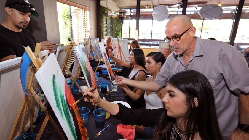 Artist Al Scholl, teaching his Art Therapy class at Inland Tavern, gives advice to student Camila Molina, at right. The students are all painting the same colorful wave scene.