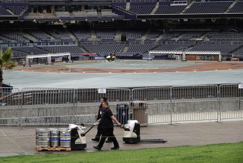 Workers transport kegs of beer at Petco Park on Thursday, the day it was announced the baseball season would be delayed by at least two weeks.