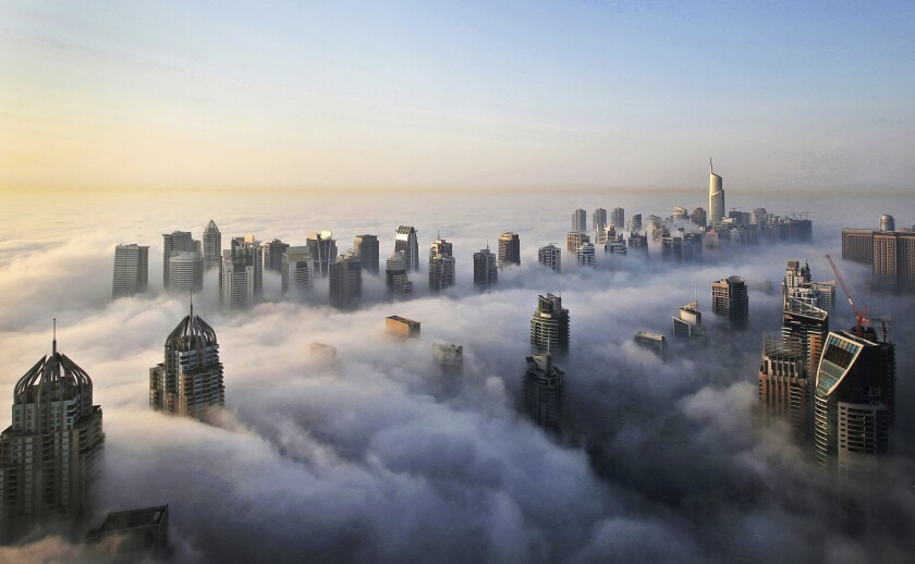 FILE - In this Monday, Oct. 5, 2015 file photo, a thick blanket of early morning fog partially shrouds the skyscrapers of the Marina and Jumeirah Lake Towers districts of Dubai, United Arab Emirates. Travel agencies in countries across the Middle East and Africa say the United Arab Emirates has temporarily halted issuing new visas to their citizens, a so-far unexplained ban on visitors amid both the coronavirus pandemic and as the UAE normalizes ties with Israel. (AP Photo/Kamran Jebreili, File)