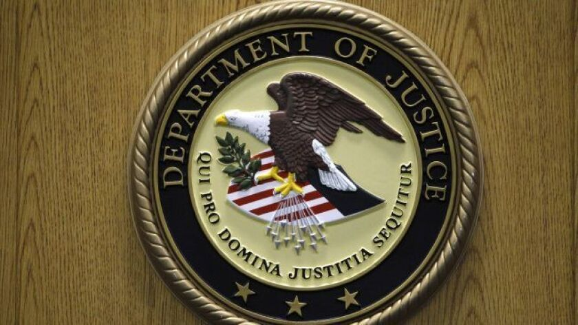 A Department of Justice logo is shown on a podium during a news conference about Novartis Pharmaceut