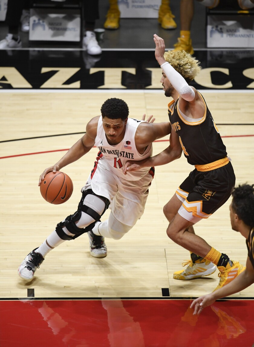 SDSU senior Matt Mitchell drives past Wyoming's Hunter Maldonado in the Aztecs' 98-71 victory on Saturday.