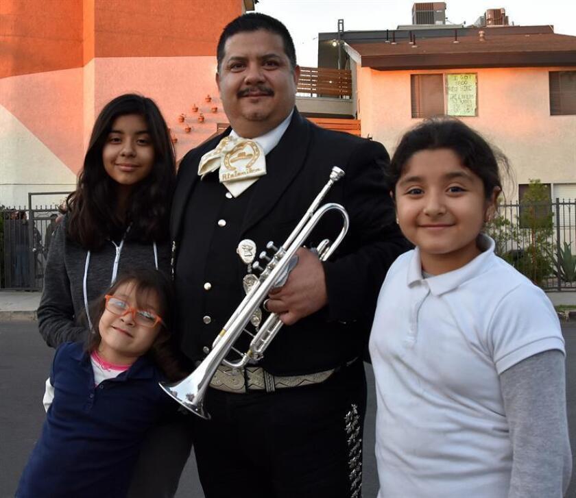 El mariachi José Luis Sandoval (c) posa junto a sus hijas Isabel (i-abajo), Jocelyn y Melissa (d) frente al edificio donde residen junto a otros mariachis en Los Ángeles (EE.UU.) hoy, jueves 15 de febrero de 2018. EFE