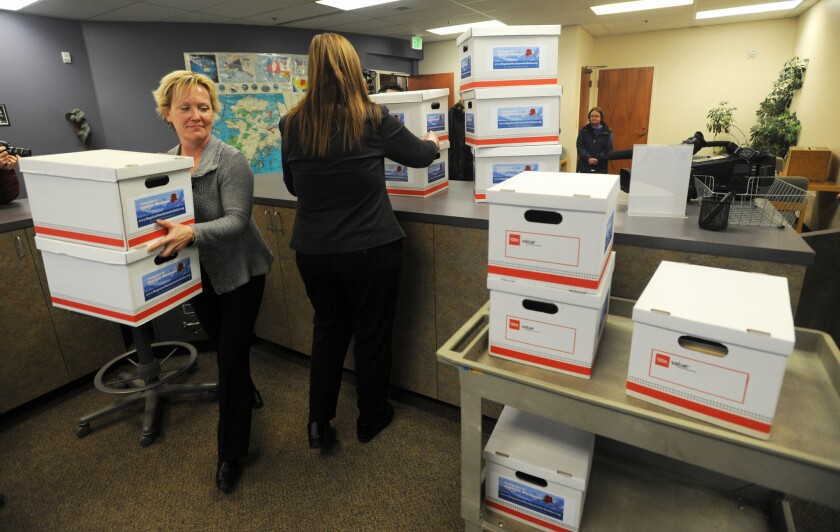 Katrin Haugh, left, and Carol Thompson of Alaska's Absentee and Petition Office begin processing signatures Jan. 8 for a proposed ballot initiative to legalize the recreational use of marijuana in the state. Enough signatures have since been verified for the measure to reach the ballot in August.