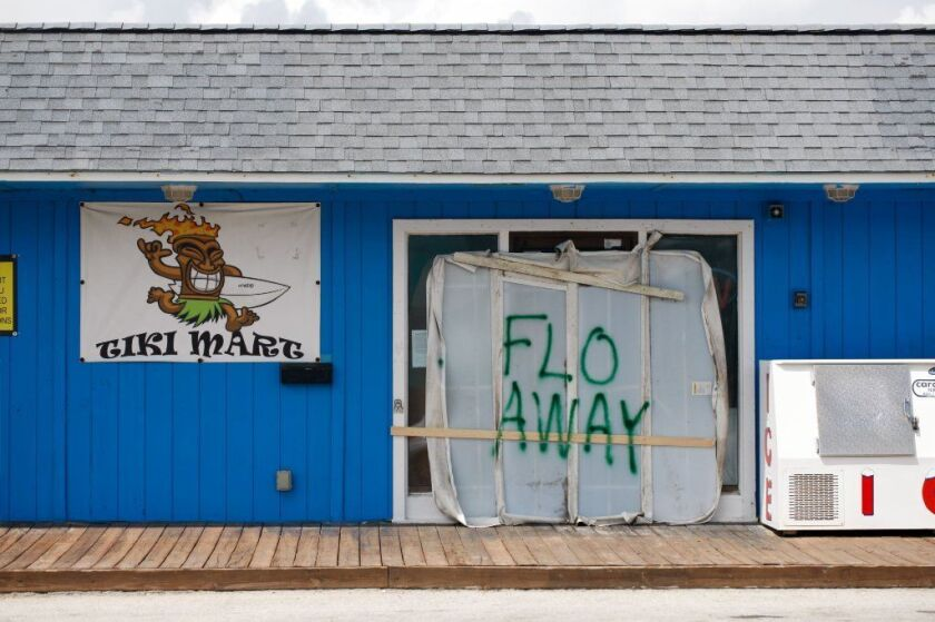 "A Tiki bar sits empty with the message ""FLO AWAY"" September 11, 2018 on Topsail Island, North Carolina, where homes and businesses have boarded up and left for higher ground before the arrival of of Hurricane Florence."