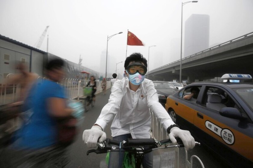 A man tries to protect himself from Beijing's thick smog in June.
