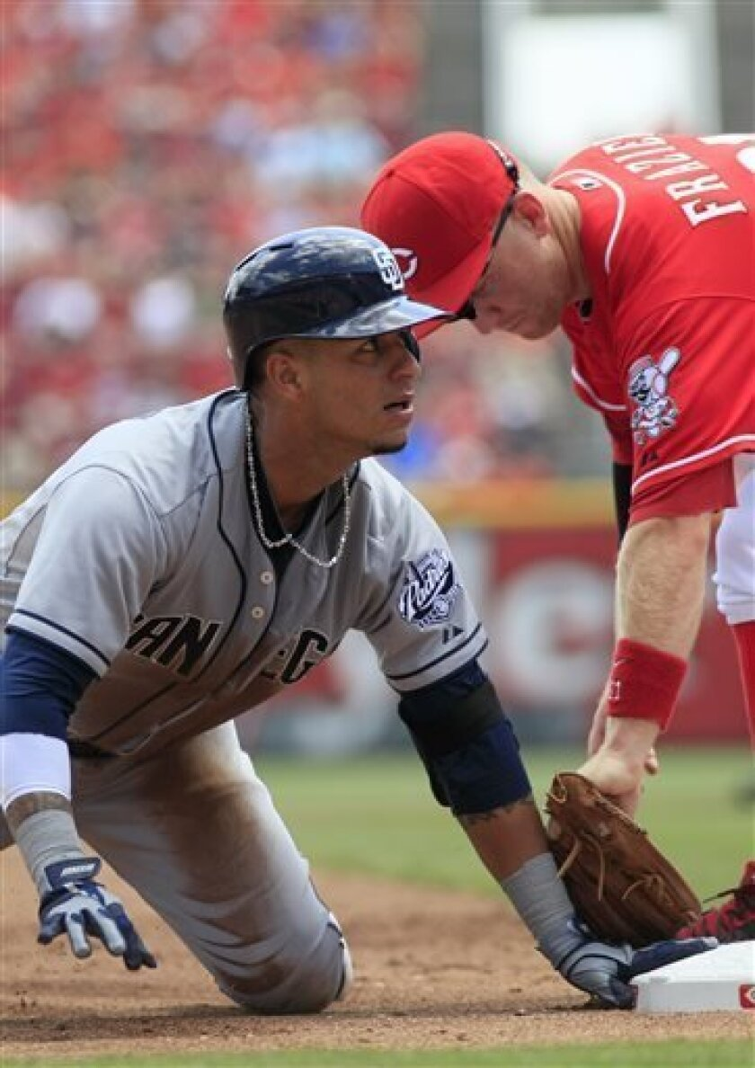 San Diego Padres shortstop Ronny Cedeno, left, is safe at third for a triple after beating the tag from Cincinnati Reds third baseman Todd Frazier, right, in the first inning during a baseball game, Sunday, Aug. 11, 2013, in Cincinnati. (AP Photo/David Kohl)