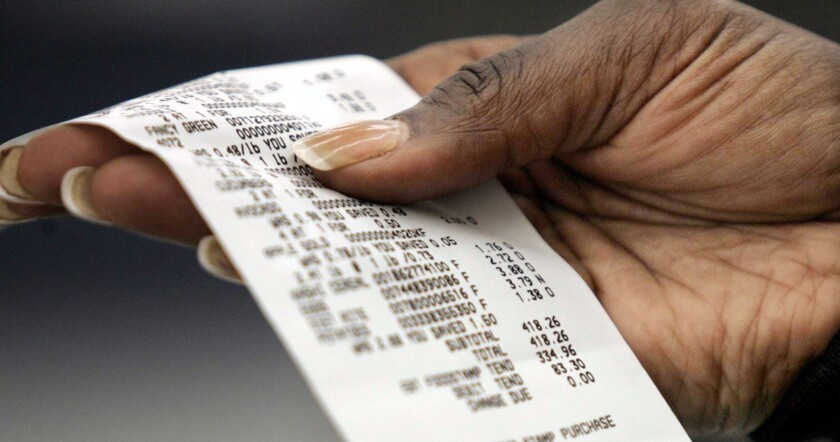 A paper receipt in a person's hand.