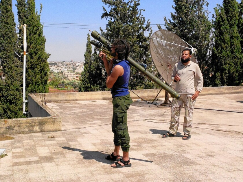 Malik Abu Iskandaroon, a rebel fighter with the Western-backed Harakat Hazm, stands on the roof of the group's air force headquarters with a Russian-made Igla anti-aircraft missile trying to target a Syrian government plane.