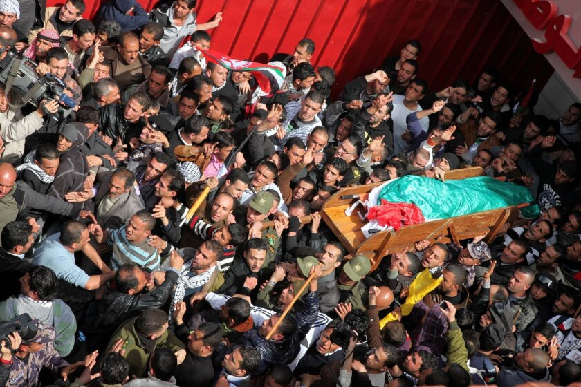 The body of Arafat Jaradat is carried through the West Bank town of Sair near Hebron prior to his funeral Monday.