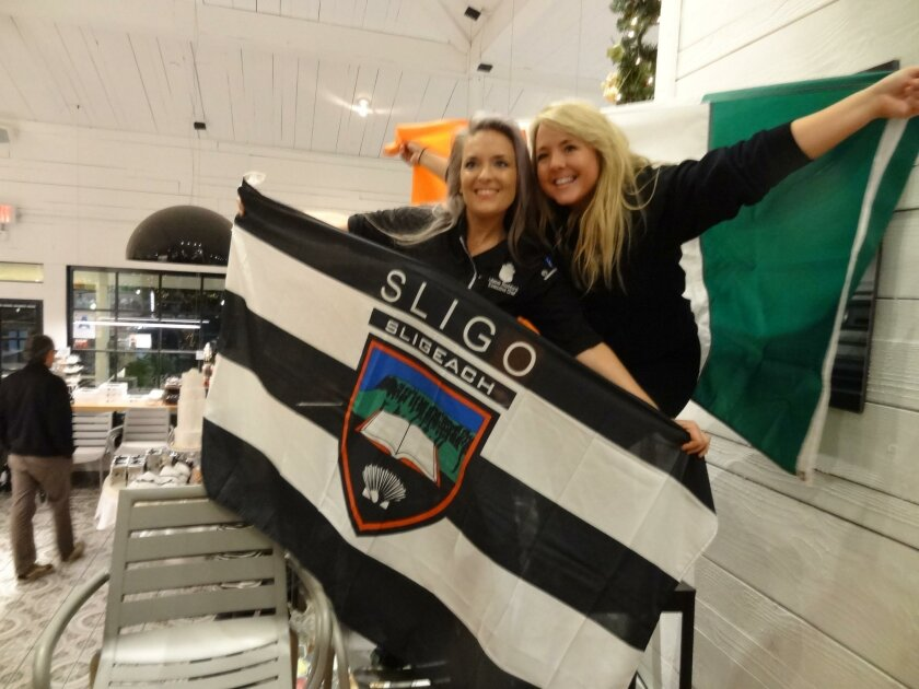 After her Food Network Holiday Baking Championship victory in December 2015, Maeve Rochford (left) and a Suger and Scribe employee celebrate, holding Irish flags.