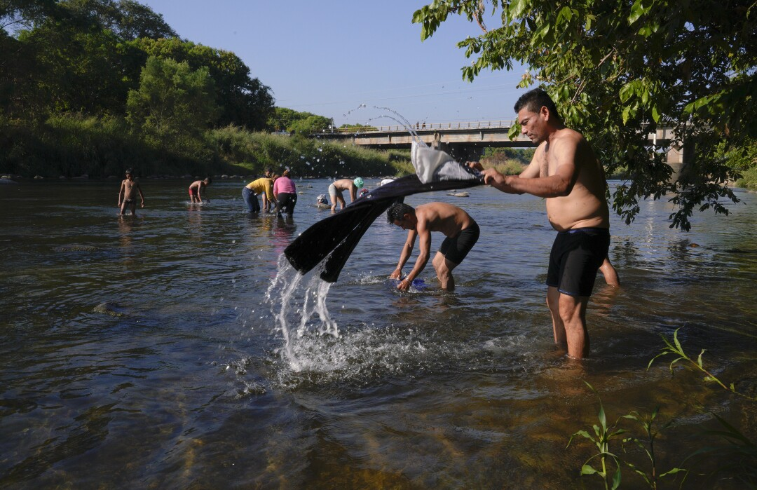 Men and women take a brief break on their journey north in January 2019 to bathe in the river in Tapachula, Mexico.