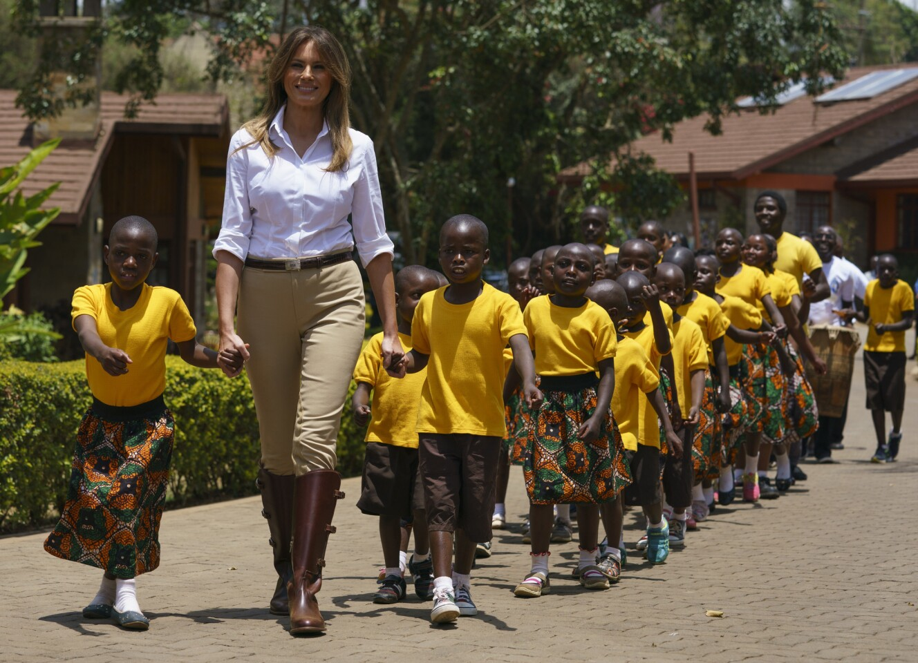 """First lady Melania Trump walks hand-in-hand with Kenyan children as she visits the Nest Orphanage in Limuru on Oct. 5, 2018. The first lady touched down in Kenya on Friday for the third stop of her visit to Africa to promote her """"Be Best"""" child betterment campaign."""