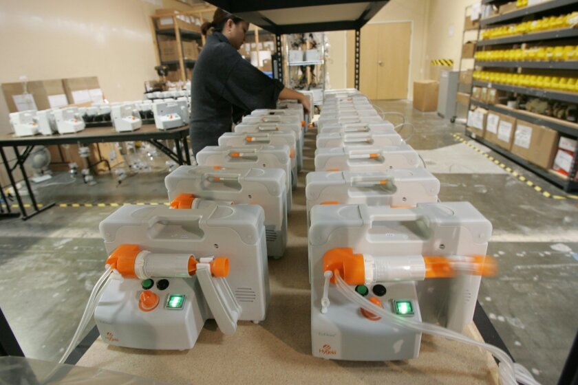 """A worker at the Hygeia factory in Vista inspects breast pumps. The company has taken a different route from most breast pump makers by marketing its products as reusable and providing instructions on disinfection by changing out certain parts. (Most breast pumps are marketed as """"single-user"""" device"""