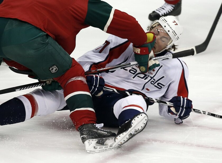 Washington Capitals' T.J. Oshie, right, takes a check by Minnesota Wild's Mikko Koivu of Finland in the first period of an NHL hockey game, Thursday, Feb. 11, 2016, in St. Paul, Minn. (AP Photo/Jim Mone)