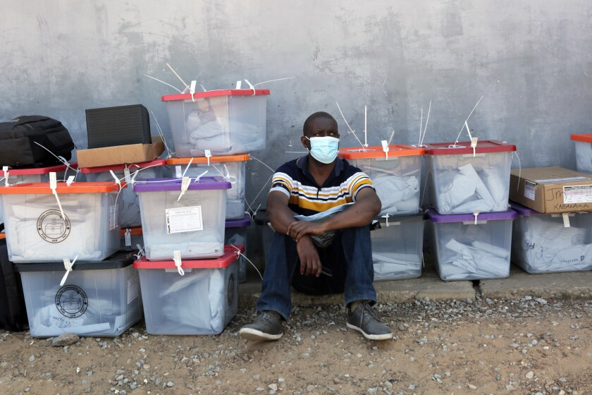 A polling agent sits next to ballot boxes as vote counting continues at various polling stations in Lusaka, Zambia, Friday, Aug. 13, 2021. Zambia's President Edgar Lungu has ordered more troops deployment in some restive parts of the country where 2 deaths were recorded on election day according to a statement issued by his office.(AP Photo/Tsvangirayi Mukwazhi)