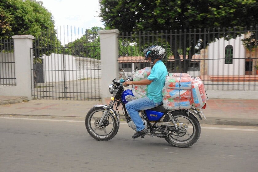 A man ferries goods that are heavily subsidized by the Venezuelan government into Cucuta, Colombia, where they are discounted but still sold at a large profit.