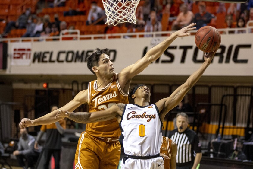 Texas forward Brock Cunningham (30) guards Oklahoma State guard Avery Anderson III (0) during the second half of the NCAA college basketball game in Stillwater, Okla., Saturday, Feb. 6, 2021. (AP Photo/Mitch Alcala)