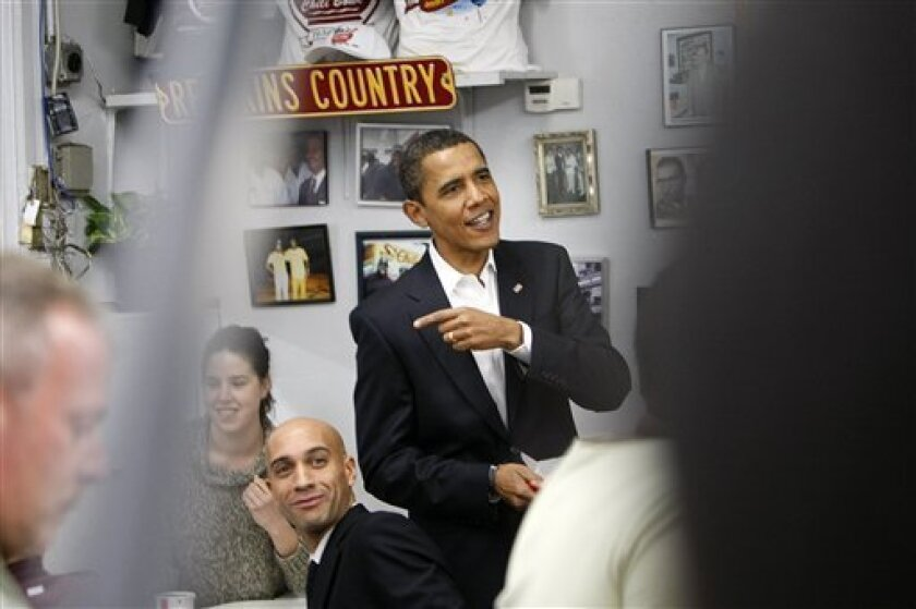 President-elect Barack Obama talks at Ben's Chili Bowl on a lunch stop with Washington Mayor Adrian Fenty, seated, in Washington, Saturday, Jan. 10, 2009. (AP Photo/Gerald Herbert)