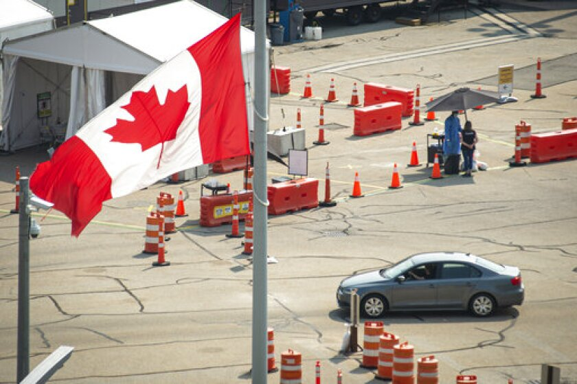 Car cross the border into Canada, in Niagara Falls, Ontario, on Monday, Aug. 9, 2021. American citizens and permanent residents are now allowed to enter Canada for non-essential purposes if they can provide proof that they've been fully vaccinated for at least 14 days. (Eduardo Lima/The Canadian Press via AP)