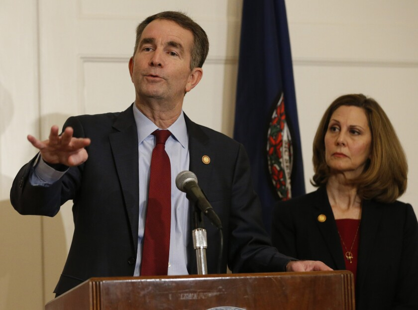 Virginia Gov. Ralph Northam, left, gestures as his wife, Pam, listens during a news conference in the Governors Mansion at the Capitol in Richmond, Va., Saturday, Feb. 2, 2019.