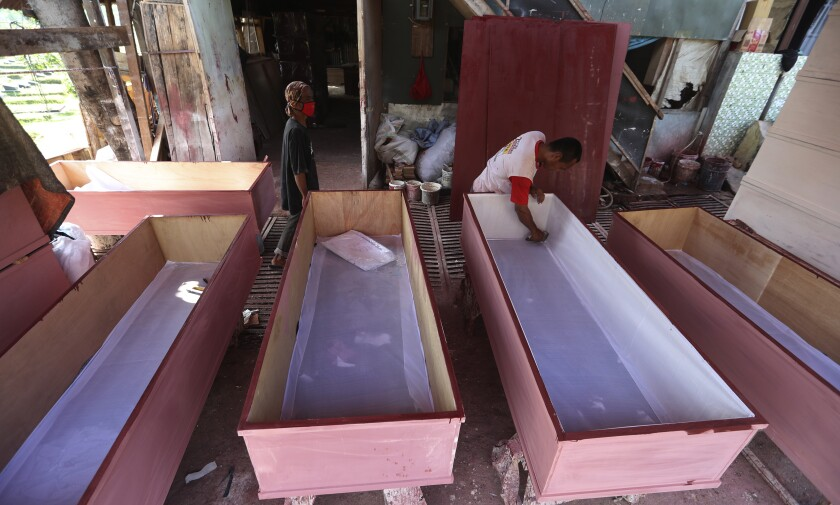 Workers make coffins to be used for victims of the coronavirus in Jakarta, Indonesia, Tuesday, July 27, 2021. Indonesia has been showing sharp increases since late June. (AP Photo/Achmad Ibrahim)