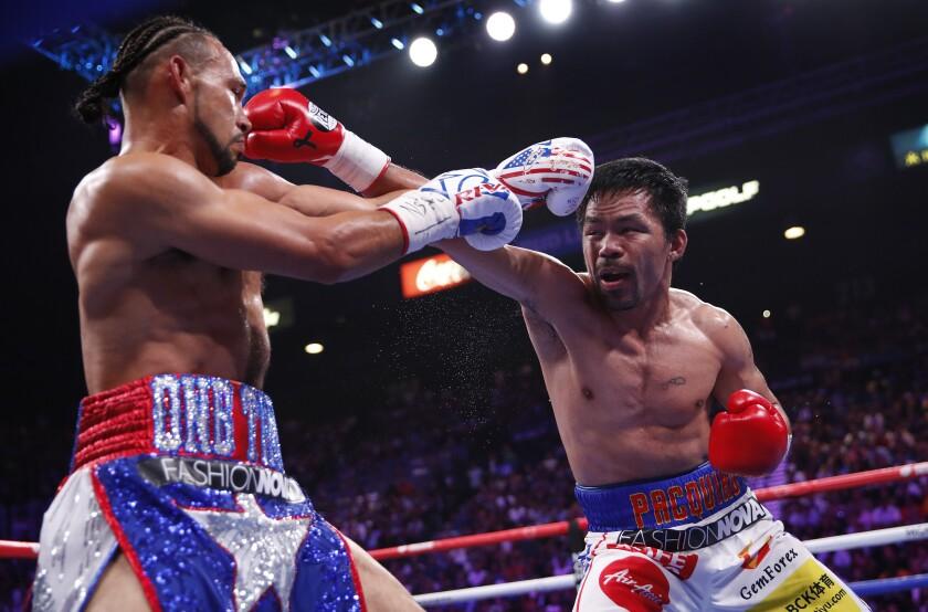 Manny Pacquiao, rechts, und Keith Thurman tauschen Schläge in der zweiten Runde ihres Titelkampfs im Weltergewicht aus.