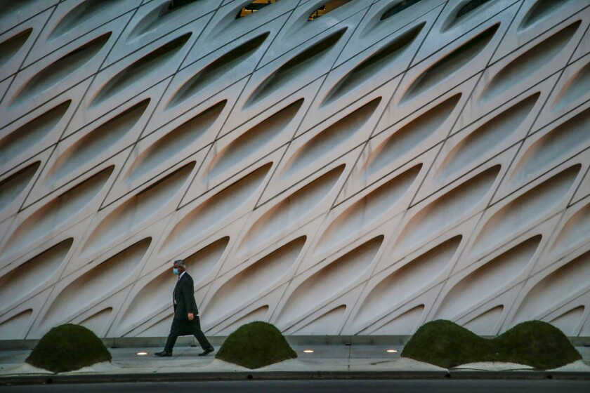 A man in a suit and a face mask walks in front of the Broad Museum.