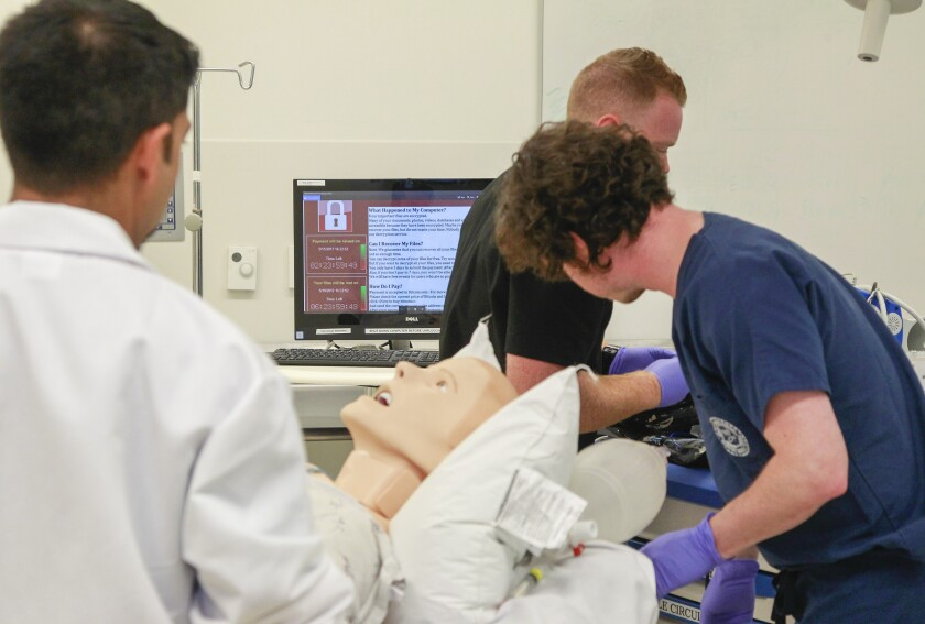 With a ransomware-locked computer in the background, CyberMed Summit participants (from left) Dr. Rahul Nene, Dr. Jordan Selzer (back), and Dr. Jeff Tully treat a medical mannequin Thursday during a cyber attack simulation at the UCSD School of Medicine.