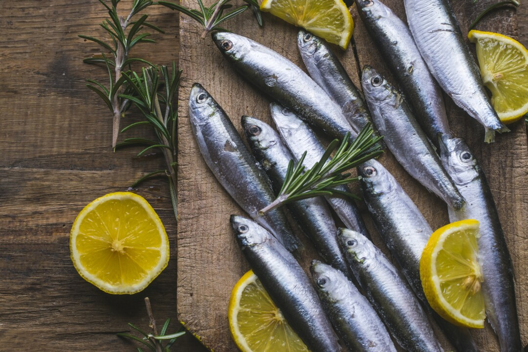 Fresh frozen sardines with lemon and rosemary on old, dark, wooden table