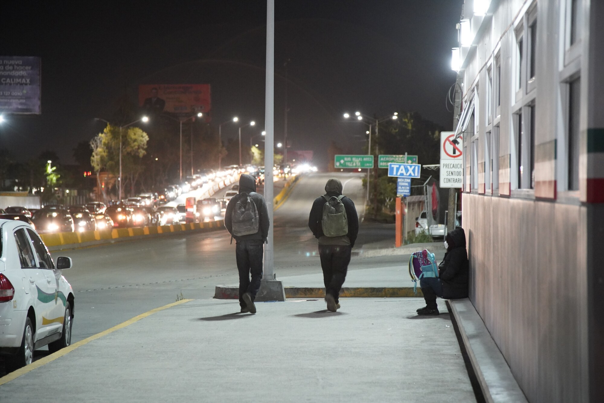 Two men recently expelled from the United States walk out of the Otay Mesa Port of Entry area