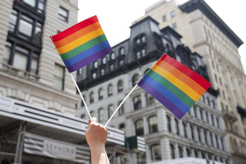 An attendee holds up flags during the New York City Pride Parade, Sunday, June 24, 2018, in New York. The percentage of LGBTQ workers who say they are closeted at work only decreased by four points since 2008.
