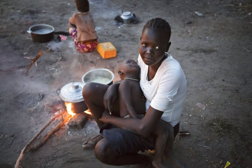 A displaced woman and baby who fled the recent fighting between government and rebel forces in Bor by boat across the White Nile, sit by a fire as they cook food in the evening in the town of Awerial, South Sudan Wednesday, Jan. 1, 2014. The international Red Cross said Wednesday that the road from