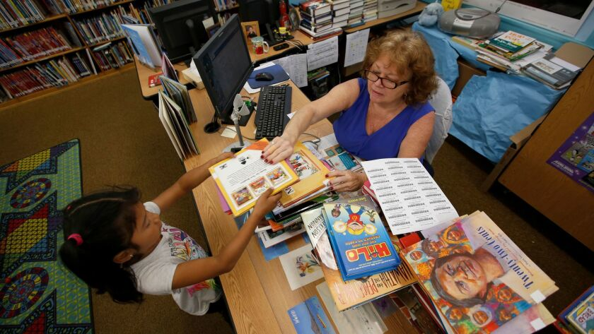Samantha Hernandez, 8, left, checks out a book in May from library aide Nina Briggs at Meyler Street Elementary School in West Carson. Briggs won't lose her job but 30 other Los Angeles Unified library aides are targeted for layoffs.