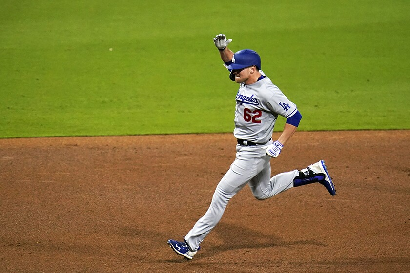 The Dodgers' Luke Raley raises a hand as he runs.