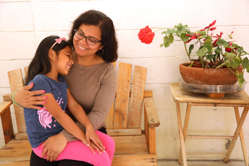 At home, DACA recipient Miriam Delgado holds her daughter Aleha Esquivel, 7, in her lap. Both are smiling.