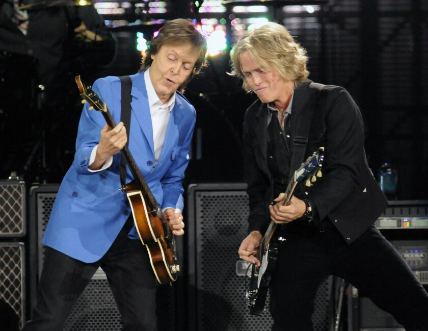 """Sir Paul McCartney, left, performs with band member Brian Ray during the Out There"""" Tour at the Times Union Center on Saturday, July 5, 2014, in Albany, N.Y. (Photo by Hans Pennink/Invision/AP)"""