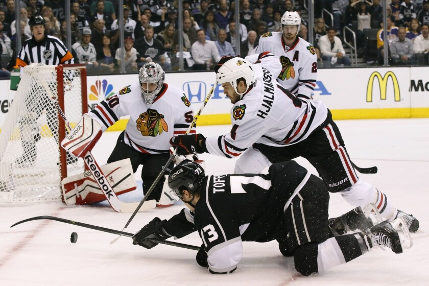 Kings forward Tyler Toffoli tries to pass the puck as he falls to the ice past Blackhawks defenseman Niklas Hjalmarsson in the first period of Game 6.