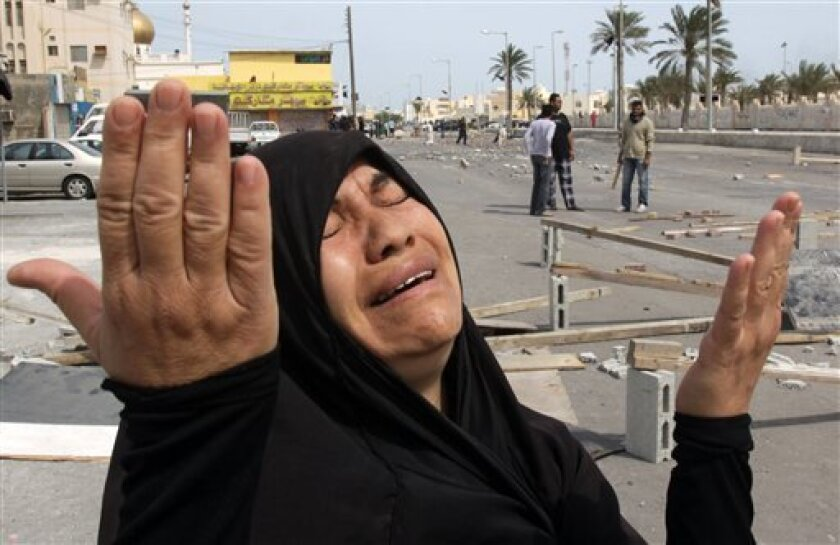 A Bahraini woman reacts, as young men and men wait in the streets behind her for government forces they expect will role into their Shiite Muslim village of Dumistan, Bahrain, southwest of the capital of Manama, Wednesday, March 16, 2011. Soldiers and riot police used tear gas and armored vehicles to drive out hundreds of anti-government protesters occupying a landmark square in Bahrain's capital, a day after emergency rule was imposed in the violence-wracked Gulf kingdom. (AP Photo/Hasan Jamali)