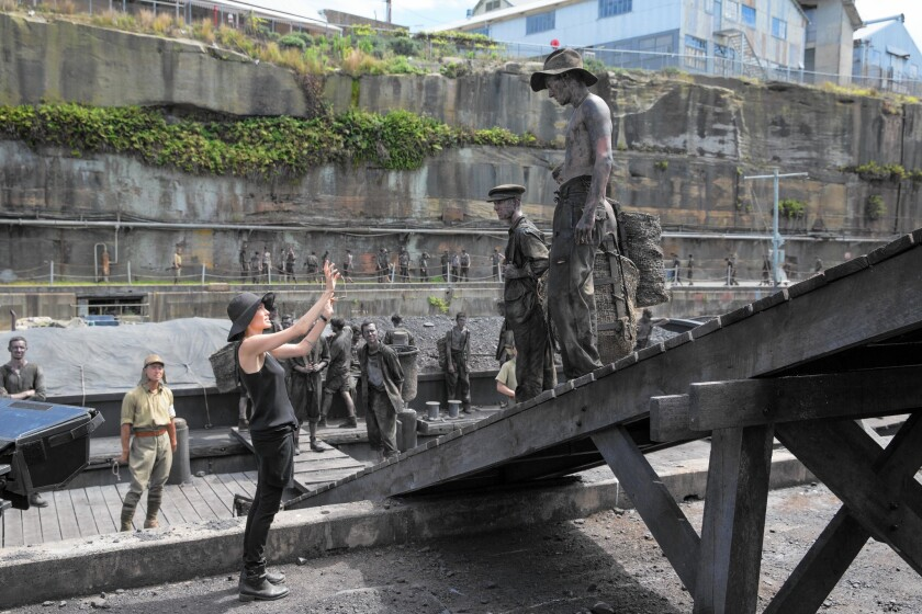 """Director Angelina Jolie works with actors portraying prisoners on the Naoetsu set (River Bank Barge) of movie """"Unbroken."""""""