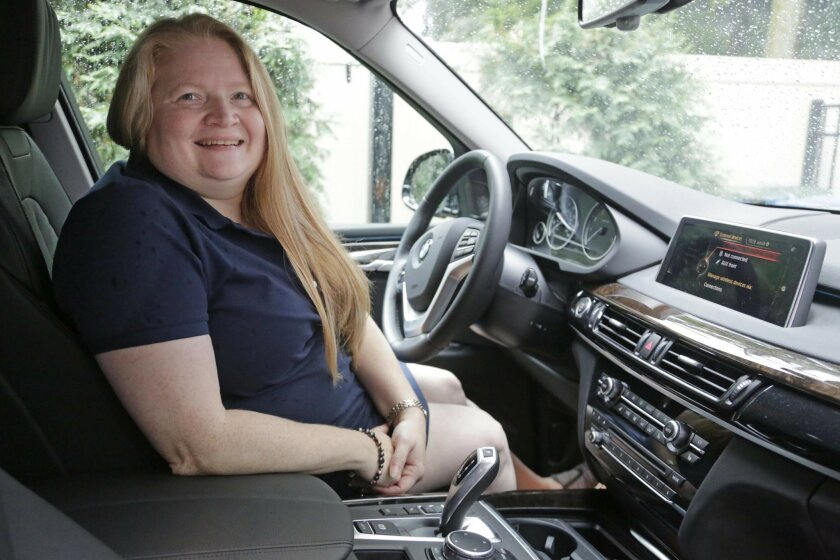 In this Aug. 24, 2016 photo, Kelly Dahle is shown with her BMW X5 in Downers Grove, Ill. (AP Photo/M. Spencer Green)
