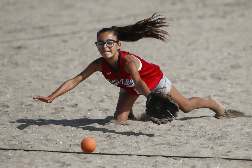"""Kaylah Franke, 11, lays out as she tries to make a catch for her team, """"Small, Medium, Tall,"""" as they face off against """"Tough Beaches"""" in the Girls 9-11 Division."""
