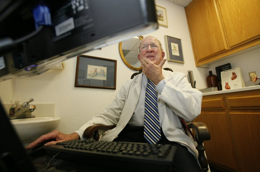 Dr. Doug Moir fills out a patient's medical history on the computer after her visit. Moir has less time for patients since electronic health record software became federally mandated. Peggy Peattie • U-T