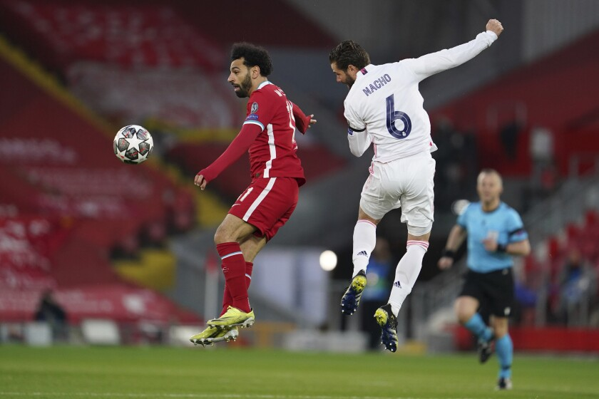 Liverpool's Mohamed Salah, left, jumps for the ball with Real Madrid's Nacho during a Champions League quarter final second leg soccer match between Liverpool and Real Madrid at Anfield stadium in Liverpool, England, Wednesday, April 14, 2021. (AP Photo/Jon Super)