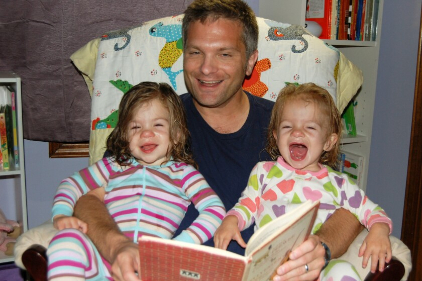 Mike Brandfon of Chicago reads to his twin daughters in 2012, when he was a stay-at-home dad after losing his job in 2009. Once the girls were nearing 3, he began looking for work again and landed a job last September.
