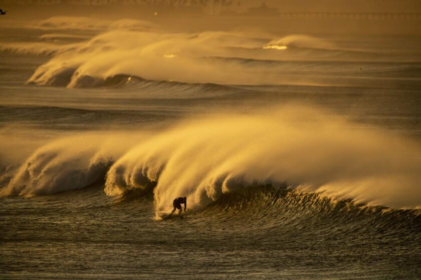 Strong Santa Ana winds blast spray from the surf off Huntington Beach.