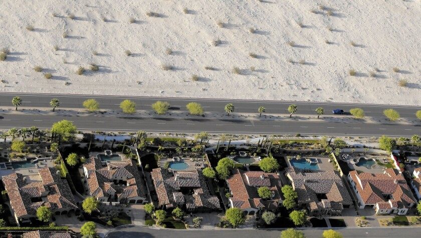 Homes with swimming pools border the desert of this neighborhood in Cathedral City, Calif. Experts say pools generally use no more water than a lawn of the same size.